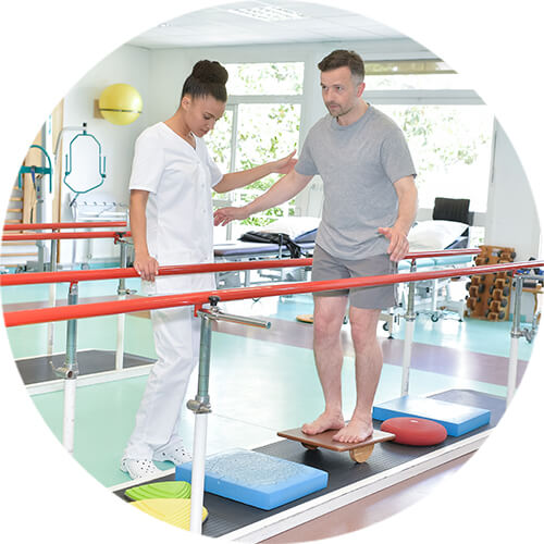 physical therapists attending to a man using parallel bars to walk